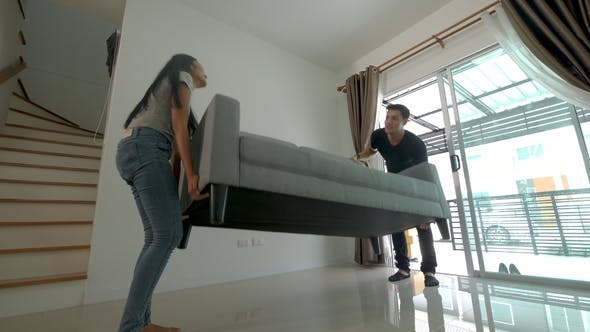 Thumbnail for Happy Young Asian Couple Moving a Sofa During Their Move Into New House