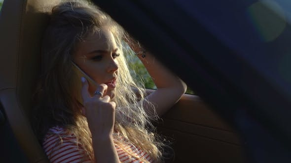 Thumbnail for Young Pretty Blonde Woman Talking on Her Phone in Her Brand-new Car with Modern Inside and Leather