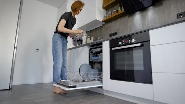 Thumbnail for Happy Young Woman Arranging Plates In Dishwasher At Home