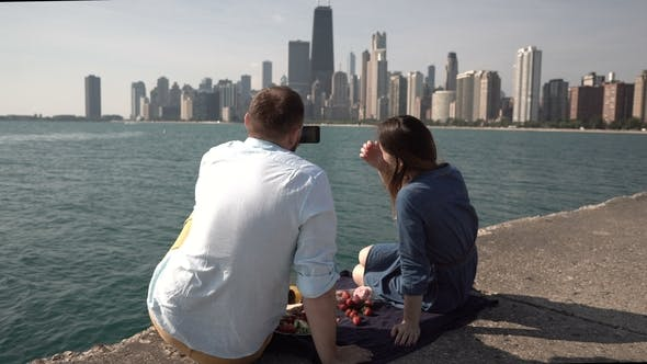 Thumbnail for Back View of Young Couple Having Picnic on the Shore of Michigan Lake in Chicago, America. Man Takes