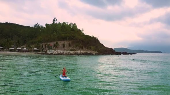 Thumbnail for Girl Swims Sitting on Paddleboard Turning From Beach To Ocean