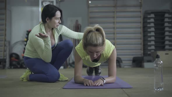 Thumbnail for Strong Young Blond Woman Standing in Plank and Raising Legs As Personal Trainer Talking. Workout of