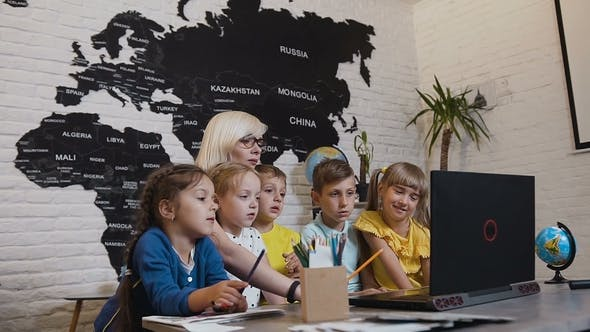 Thumbnail for Young Woman Teacher Discussing a Computer Program with a Group of Pupils. Female Teacher Using