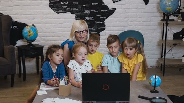 Thumbnail for Happy Teacher Using Laptop with Pupils in the Classroom of Geography