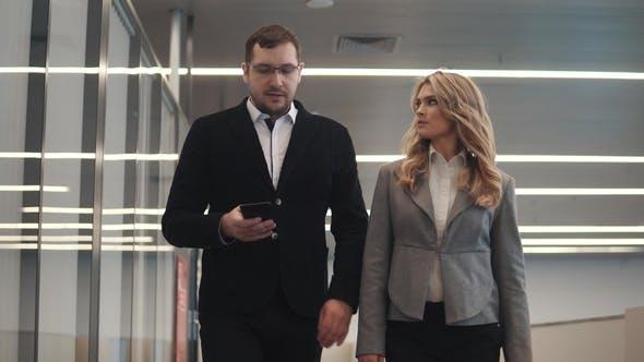 Thumbnail for Ein Mann und eine Frau spazieren im Foyer des Business Centers und sprechen Sie unterwegs