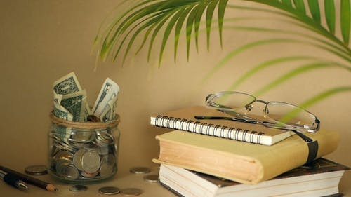 Books with Glass Penny Jar Filled with Coins and Banknotes. Tuition or Education Financing Concept