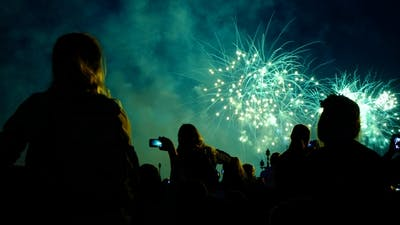 Crowd of People Looks at the Fireworks at Night. Multicolored Pyrotechnic Show on the Holiday