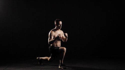 Bodybuilder führt Sprünge mit Ausfallschritten in einem dunklen Fitnessraum, trainiert seine Beinmuskulatur und