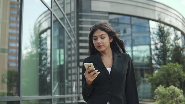 Thumbnail for Business Woman Prints a Message on a Mobile Phone. Portrait of a Woman in Business Clothes