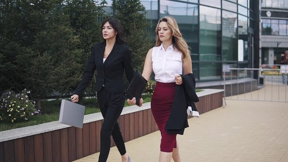Thumbnail for the Girl in a Business Suit Comes with a Colleague in a Skirt and Blouse. Business Women Walking