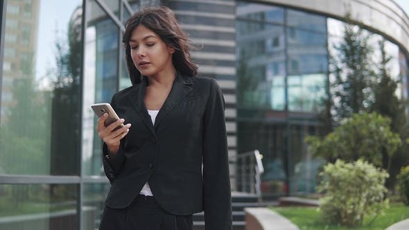Thumbnail for Attractive Business Woman Uses a Smartphone on the Background of a Modern Business Center