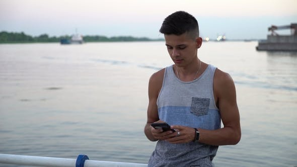 Cover Image for Young Man Stands and Touches His Phone at a River Quay at Sunset in Summer