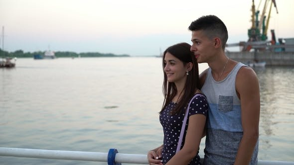 Cover Image for Young Man Embraces His Girlfriend and Chats Romantically on a Quay at Sunset