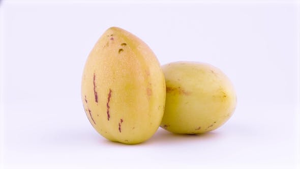 Thumbnail for Two Whole Mature Yellow Pepino Fruits. Rotating on the Turntable. Isolated on the White Background