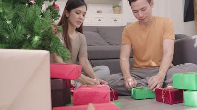 Asian couple packing and wrapping Christmas present decorate their living room at home in Christmas.