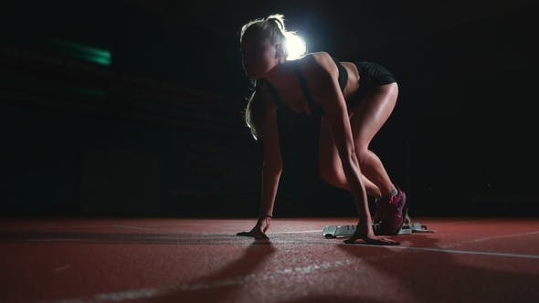 Thumbnail for Slender Young Girl Athlete Is in Position To Start Running in the Pads on the Track in