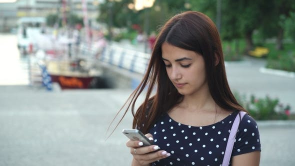 Cover Image for Stylish Girl Is Texting and Browsing the Net on Her Phone on a Riverbank in Summer