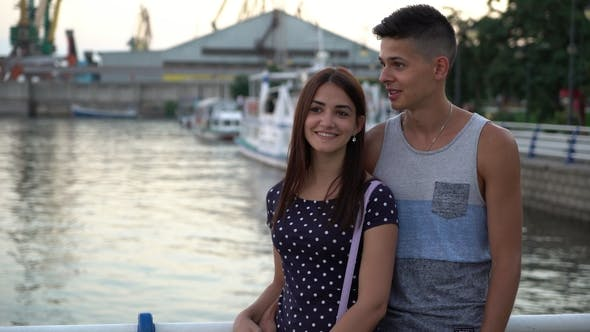 Thumbnail for Young Man Embraces His Girl and Talks Romantically on a River Quay at Sunset