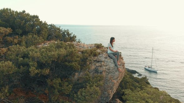 Thumbnail for Woman Sits on a Boulder and Watches Seascape