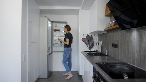 Thumbnail for Alone Young Woman Is Getting Eggs From Fridge in Her Kitchen in Morning, Preparing for Cooking