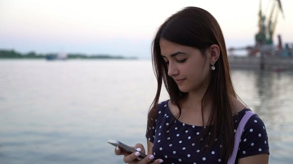 Thumbnail for Young Woman Standing and Texting on Her Phone on a River Quay in Summer