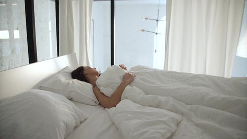 Sleep. Woman Sleeping In Bed With White Bedding At Light Bedroom