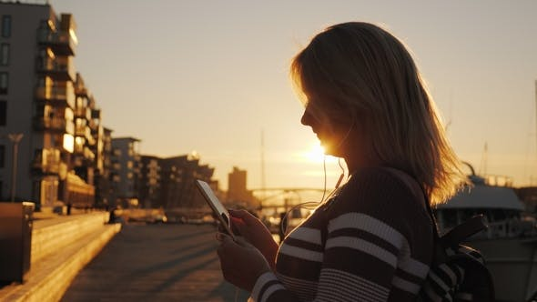 Thumbnail for A Woman in Headphones Uses a Smartphone on the Pier on the Background of Private Yachts. At Sunset
