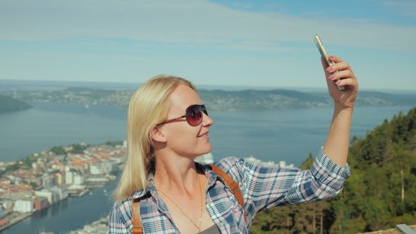 Thumbnail for Woman Tourist Taking Pictures of Herself Against the Background of the City of Bergen in Norway