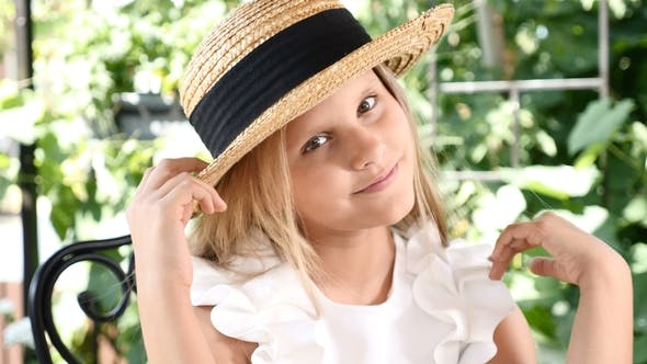 Portrait of Blond Attractive Girl Smiling, Touching Her Hair with a Straw Hat On. Lifestyle. Happy