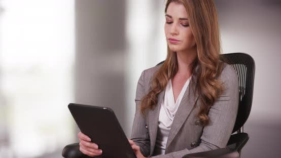 Thumbnail for Businesswoman in her 20s using tablet while sitting on her chair. Woman intern working on tablet in