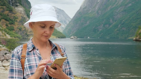 Cover Image for An Active Woman Uses a Smartphone on a Fjord in Norway. Always in Touch, Technology on the Road