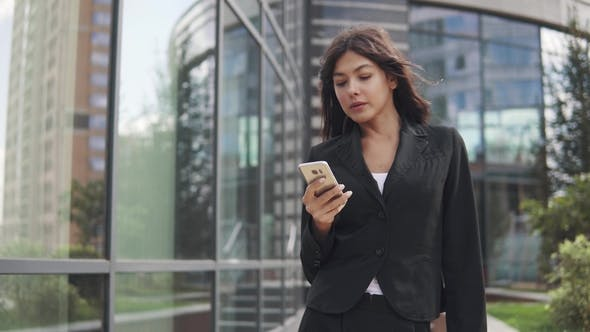 Thumbnail for Attractive Girl in a Business Suit Uses a Smartphone. Young Business Woman Texting a Message on a