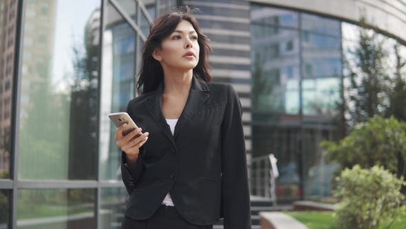 Thumbnail for Beautiful Young Woman in a Business Suit Using a Smartphone. Business Woman Texting a Message on a