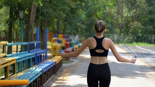 Thumbnail for Back View on Young Athlete Woman in Comfortable Sport Outfit Jumping Rope on a Sports Field in the