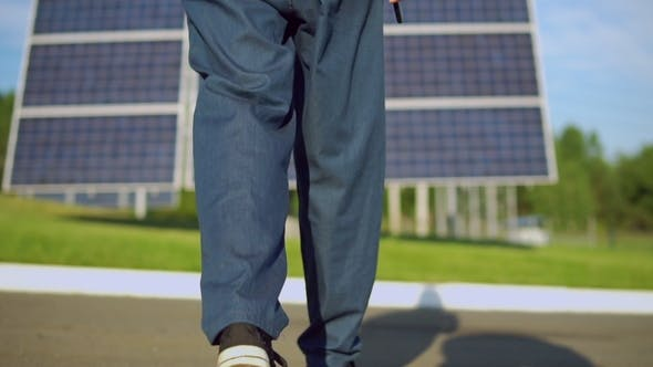 Thumbnail for Worker Wearing Blue Denim Walking To the Solarcell Battery