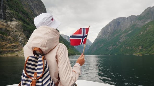 Thumbnail for A Tourist with a Flag of Norway Stands on the Nose of a Cruise Ship. Journey Through the Picturesque