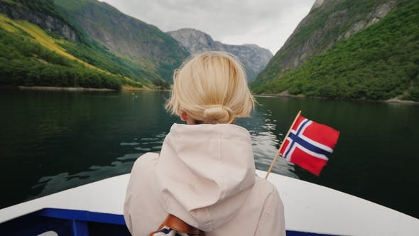 Thumbnail for A Woman with the Flag of Norway Stands on the Nose of a Cruise Ship, Sails on a Picturesque Fjord