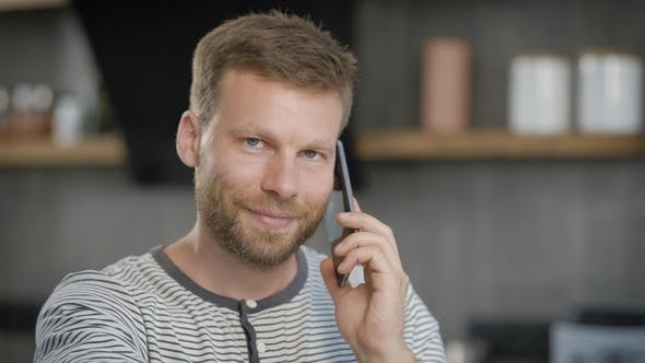 Thumbnail for Smiling Handsome Man Is Talking By Mobile Phone Sitting in His Home, Looking at Camera and on Sides