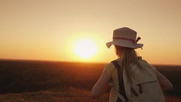 Thumbnail for A Cheerful Girl Runs Lightly Along a Country Road Towards the Setting Sun
