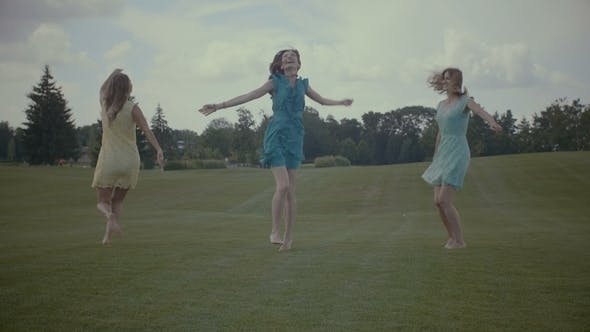 Cover Image for Carefree Women Jumping on Green Grass in Summer
