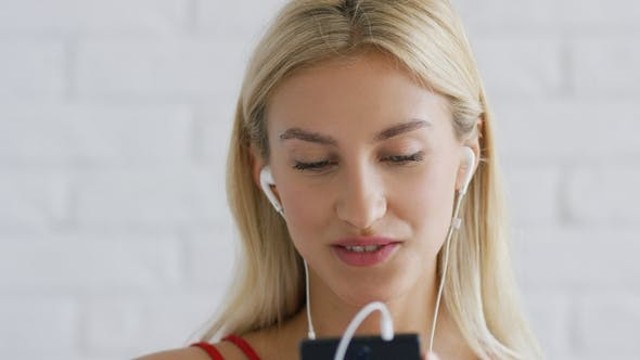 Thumbnail for Pretty Lady in Earphones Browsing Smartphone