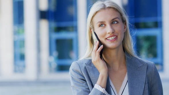 Cover Image for Cheerful Businesswoman Talking on Phone Near Building
