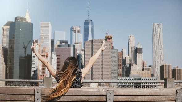 Thumbnail for Back View of Happy Female Traveler with Long Hair Blowing in the Wind Enjoying Amazing Manhattan