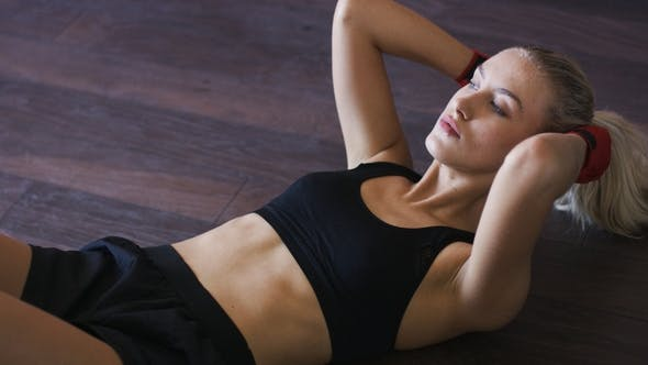 Sporty Woman Doing Abdominal Crunches On Floor By Daniel Dash On