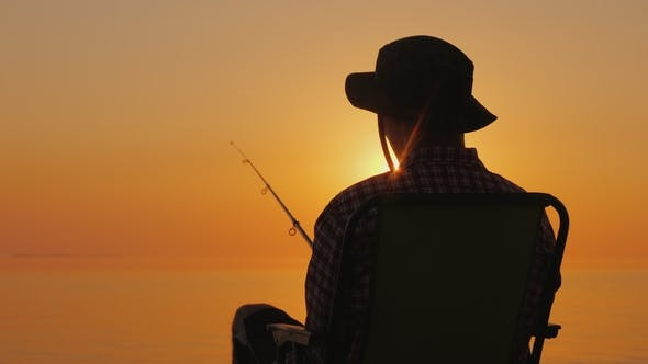 Cover Image for Rear View - a Man Sitting on the Seashore, Fishing with a Fishing Rod