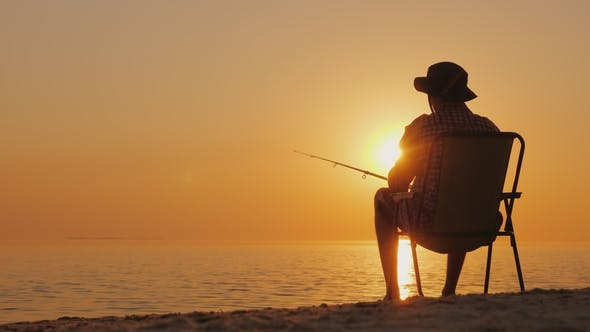 Thumbnail for A Young Man Is Sitting on the Seashore, Fishing. Relaxing in the Open Air