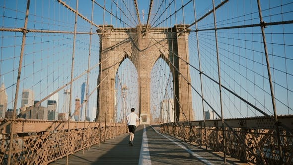 Thumbnail for Male Sportsman Running Along Brooklyn Bridge, New York on a Sunny Summer Day. Beautiful Architecture