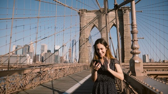 Thumbnail for Attractive Adult European Woman Talks To Friends Using Smartphone Video Call App at Brooklyn Bridge