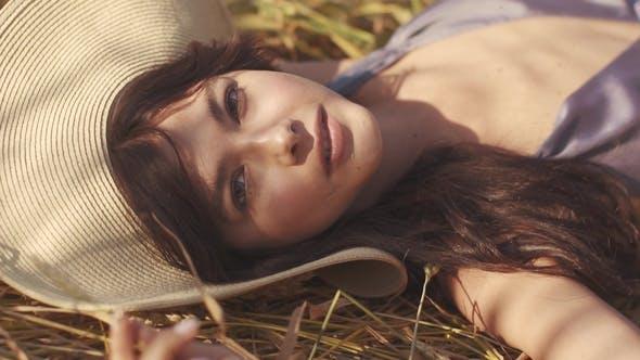 Thumbnail for Charmantes Mädchen in einem Strohhut liegt auf dem Feld beobachten und lächelnd bei der Kamera
