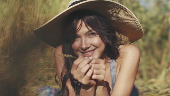 Thumbnail for Porträt eines charmanten jungen Mädchens in einem Strohhut. Ein Mädchen mit ungewöhnlichen Augen sieht und lächelt bei der